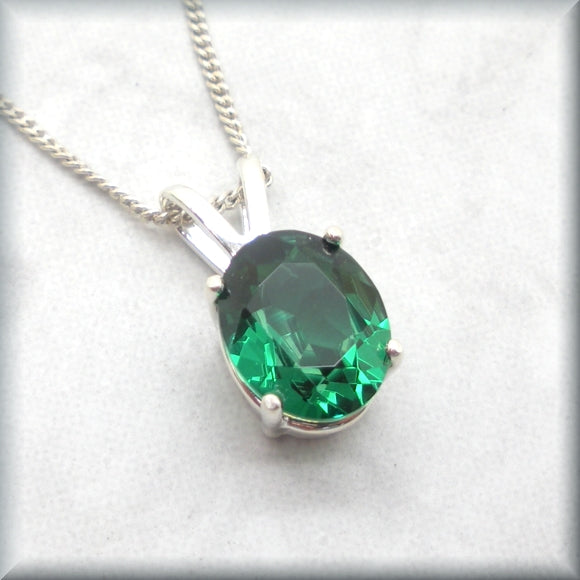 Oval cut simulated emerald on sterling silver curb chain