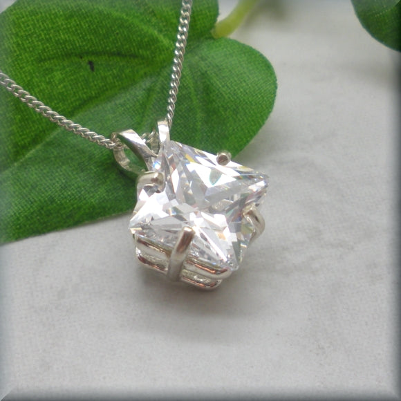 White CZ necklace set in sterling silver displayed against a leaf