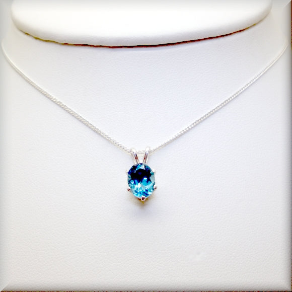 Six prong setting surround an oval London blue topaz