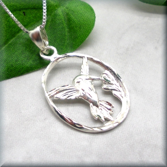 Oval hummingbird pendant with flower accent