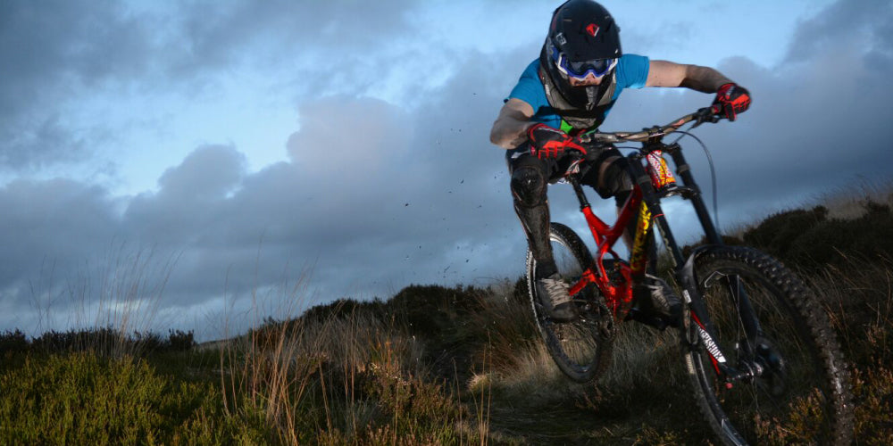 UK rider Danny Wilson ina low tuck carries termendous speed through a downhill singletrack in the grass covered hills of United Kingdom. He is wearing the red and black THE-Industries T3 full face helmet, Tek2 Shorts , Hex gloves, and F2 storm shin guards