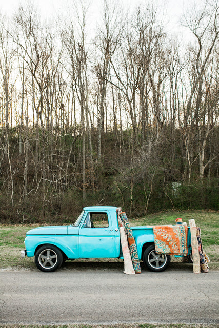 blue vintage rug truck with rugs
