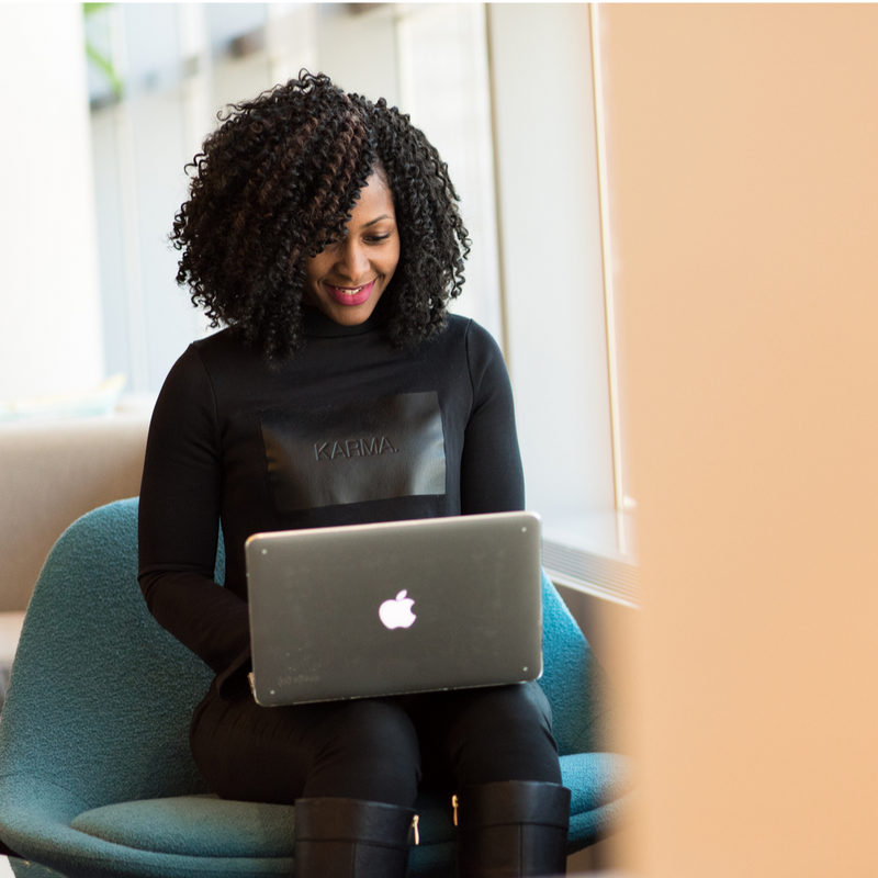 Black woman in a teal chair working on a Mac Book. Woman is smiling, wearing black clothes and in front of a window.