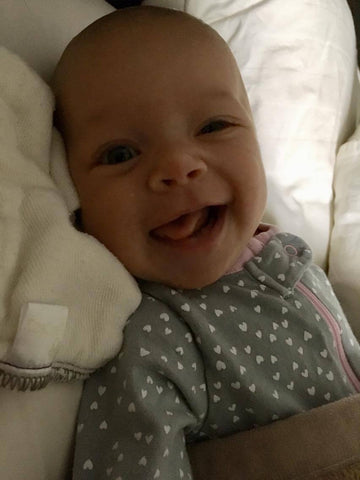 Her purposeful first smile, making everything worth it.
