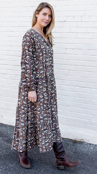 Woman in mid-calf tiered rayon, bohemian style dress with long sleeves. Hand block-printed fabric in brown and dusty blue with cream lotus shaped flower. Long sleeves