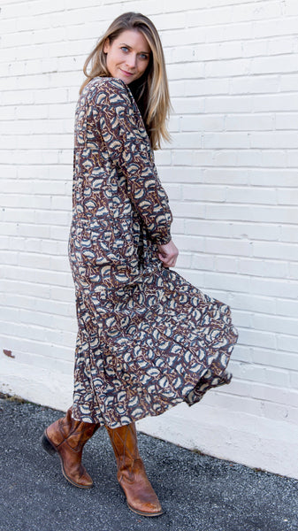 Side view of woman in mid-calf tiered rayon, bohemian style dress with long sleeves. Hand block-printed fabric in brown and dusty blue with cream, lotus shaped flowers. Long sleeves