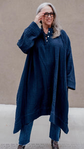 Mature woman wearing generously sized rustic textured organic cotton muslin dress in rich navy. blue. Neru placket collar with three mother of pearl buttons. Generous pockets. Uneven hem. High in front and long on sides. Long Sleeves and generous sleeve hem.