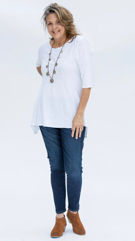 Stylish middle aged woman wearing natural linen cotton jersey long tunic in bright white over jeans and ankle boots. It is paired with a coin on leather handcrafted necklace