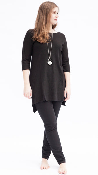 Stylish woman wearing natural linen cotton jersey tunic in black over black jeans paired with a religious charm necklace