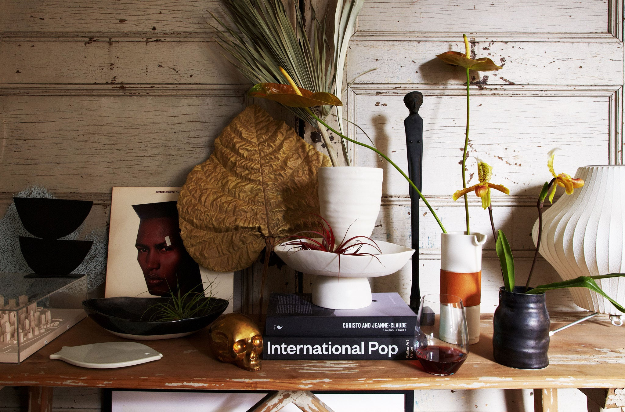 DBO HOME ceramic vases and bowls on wooden table with decorative leaves, flowers, books and art as styled by Marcus Hay