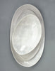 Stack of DBO HOME Honeycomb Handmade Porcelain Oval Serving Platters and Bowl