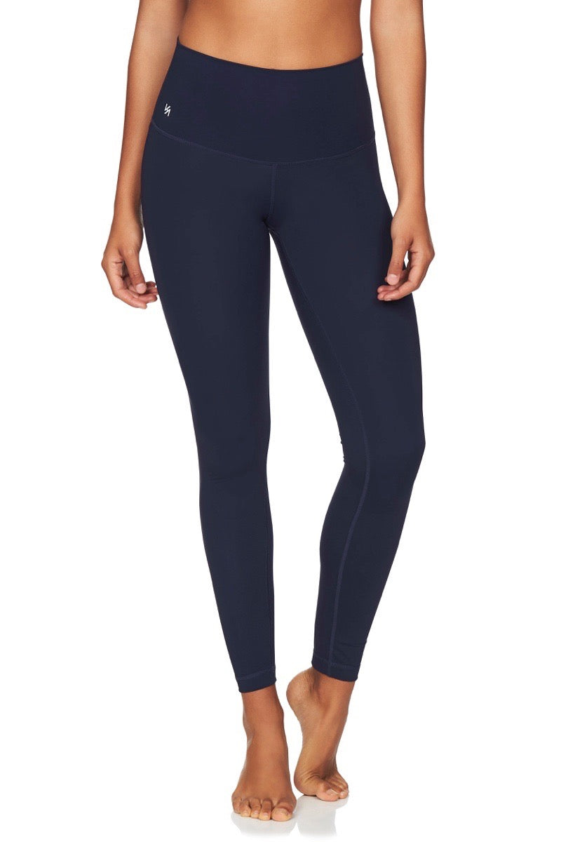 Front view of model wearing high waisted navy compression yoga pants