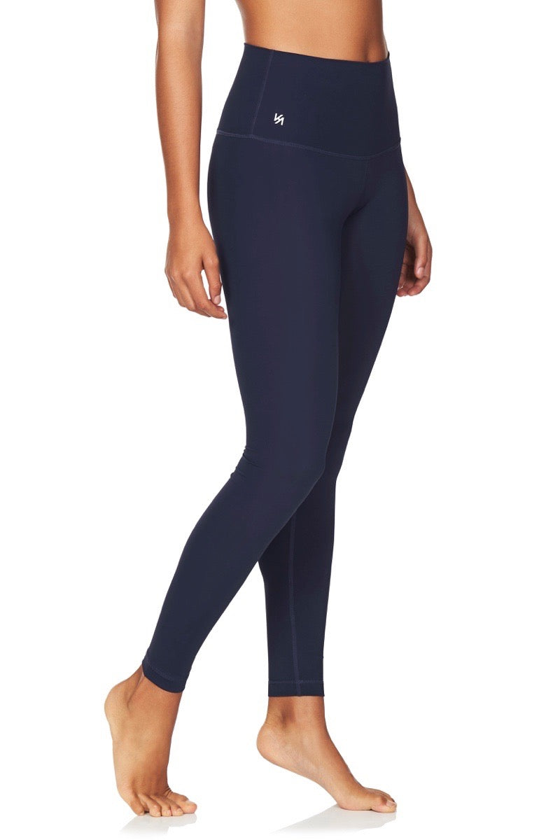 Side view of model wearing navy high waisted compression tights