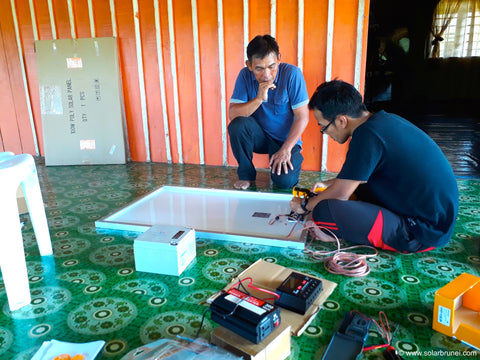 Our engineer, Fauzi showing Awan how to wire the solar panel to its components.