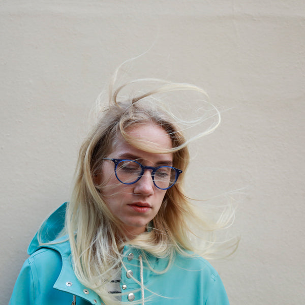 Windswept blonde female, wearing blue spectacle frame.