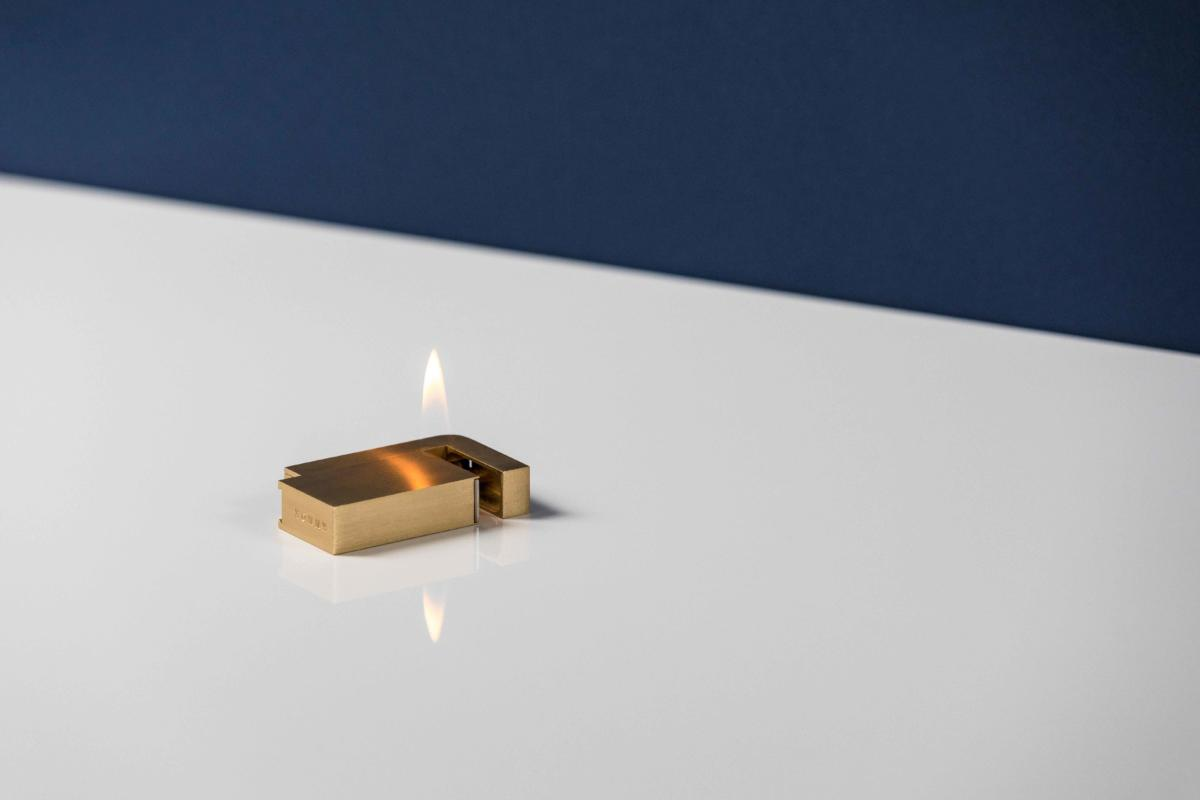 Ignited KNOXX lighter laying on desk. Photographed by Ash James.