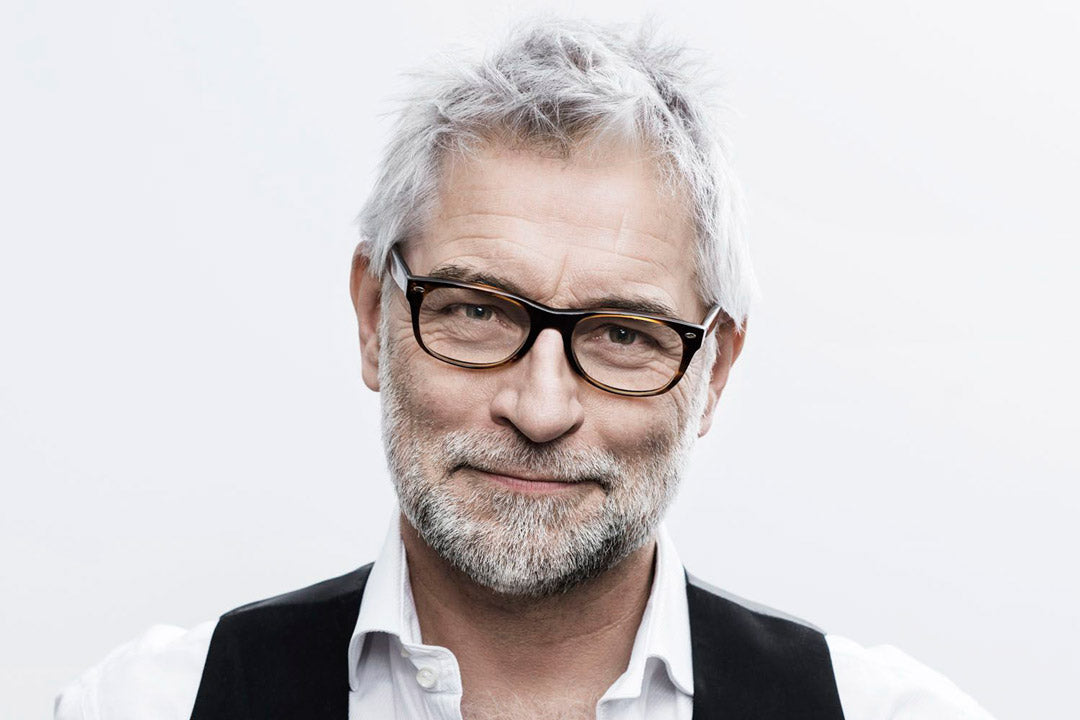 A grey haired man with grey beard wearing a rectangular dark tortoise eyeglasses frame