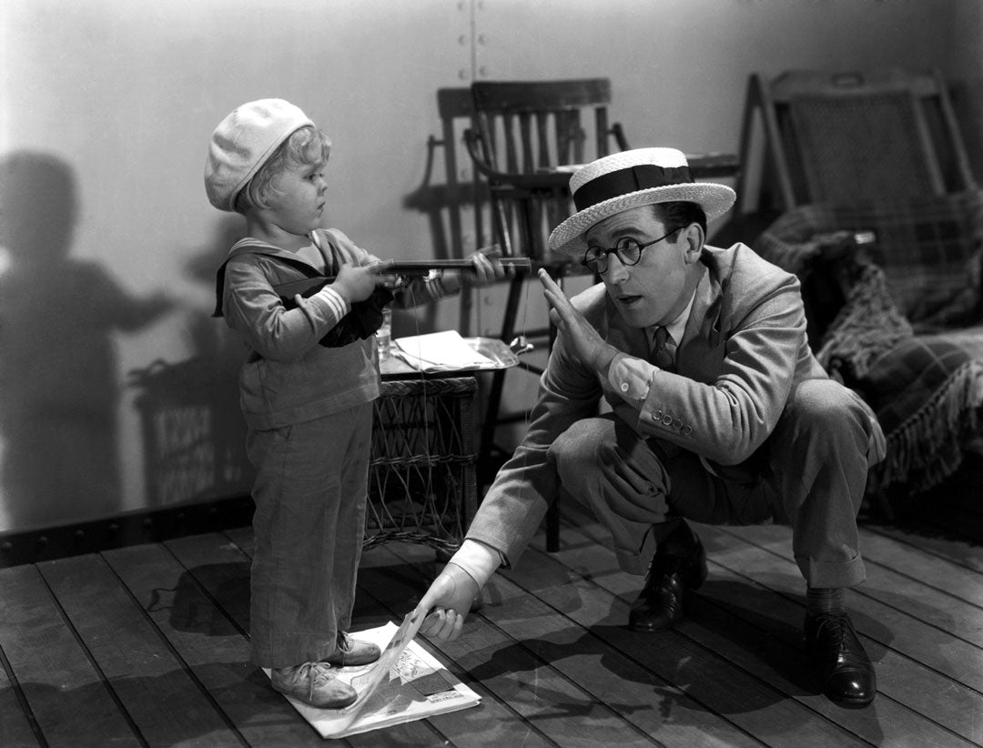 Actor Harold Lloyd crouching beside child pointing gun at him