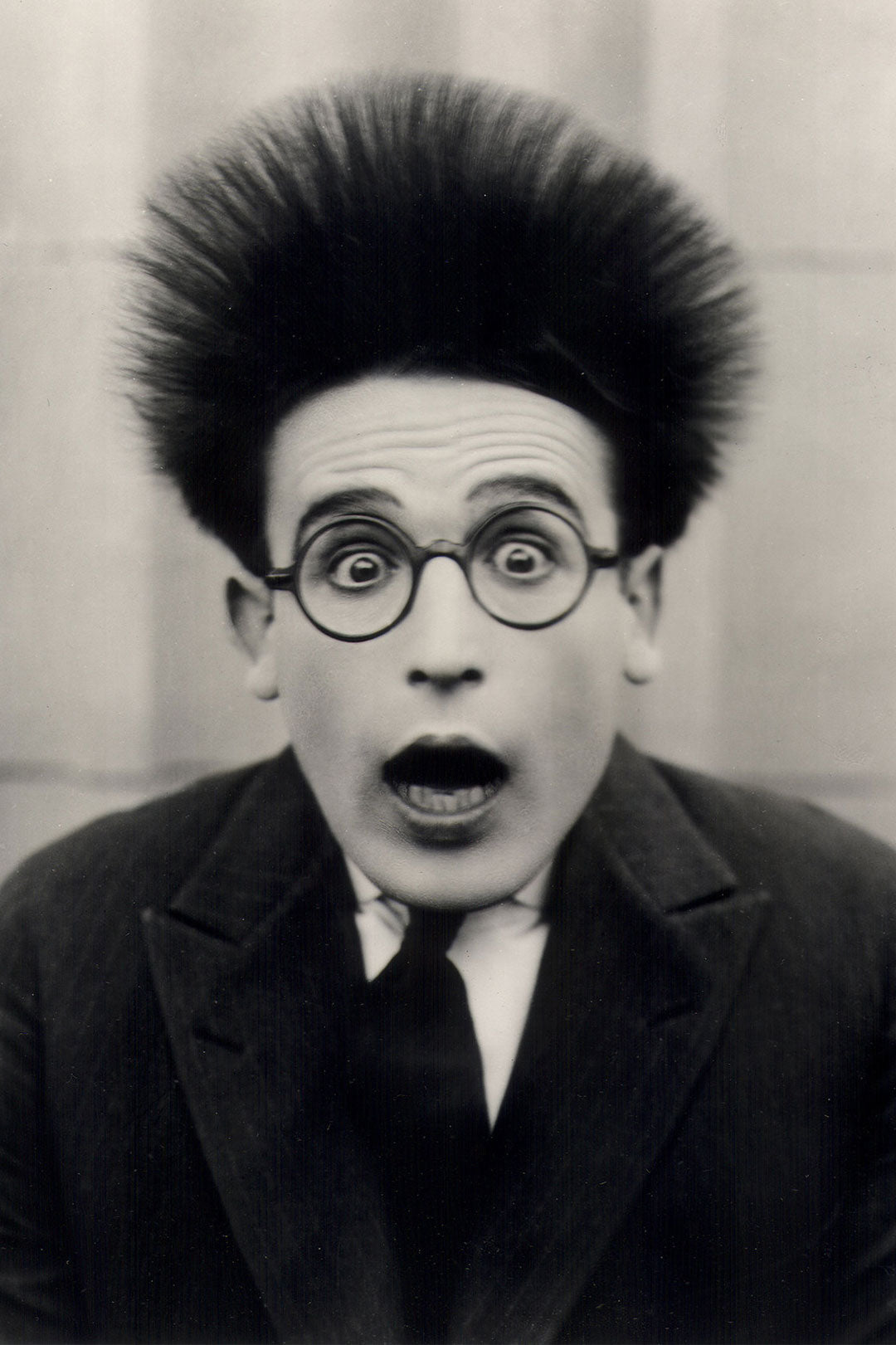Actor Harold Lloyd with his hair standing up wearing his round spectacles