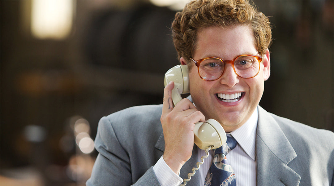 Actor Jonah Hill talking on the phone wearing round glasses and a suit