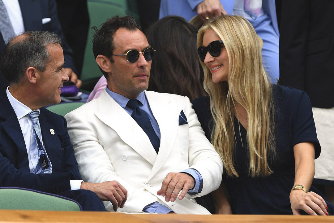 Actor Jude Law wearing white suit and round sunglasses at Wimbledon