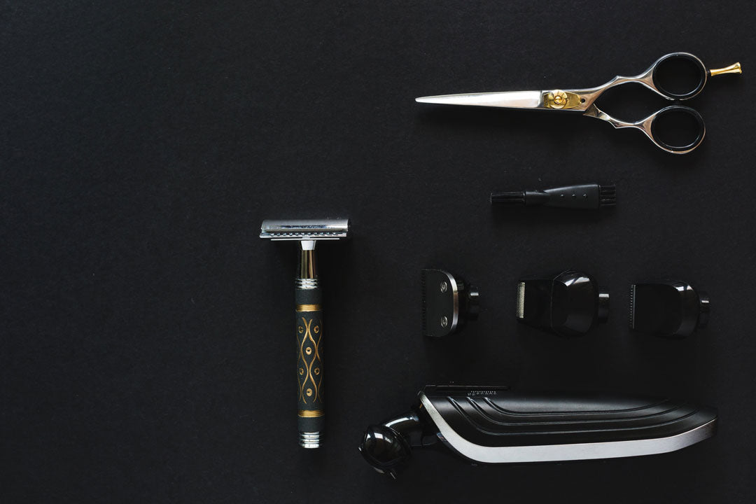 Aerial layout of men's grooming utensils on black background