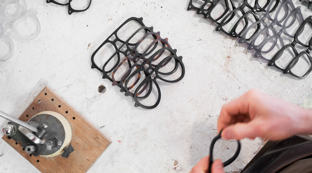 Aerial view of aviator sunglasses being handmade on white workbench