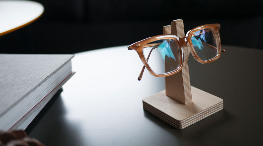 Amber eyeglasses resting on wooden glasses holder