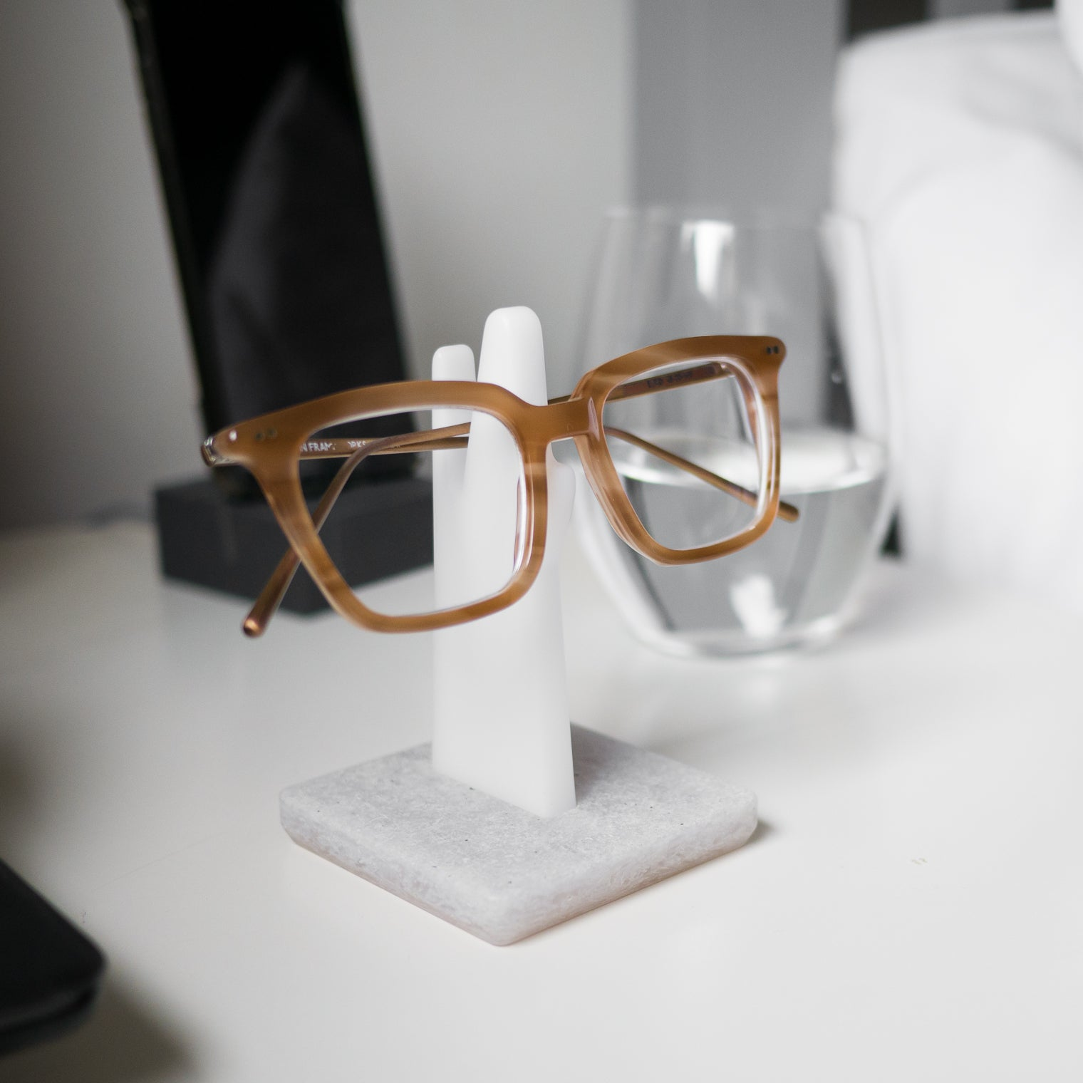 Amber glasses resting on white spectacle stand