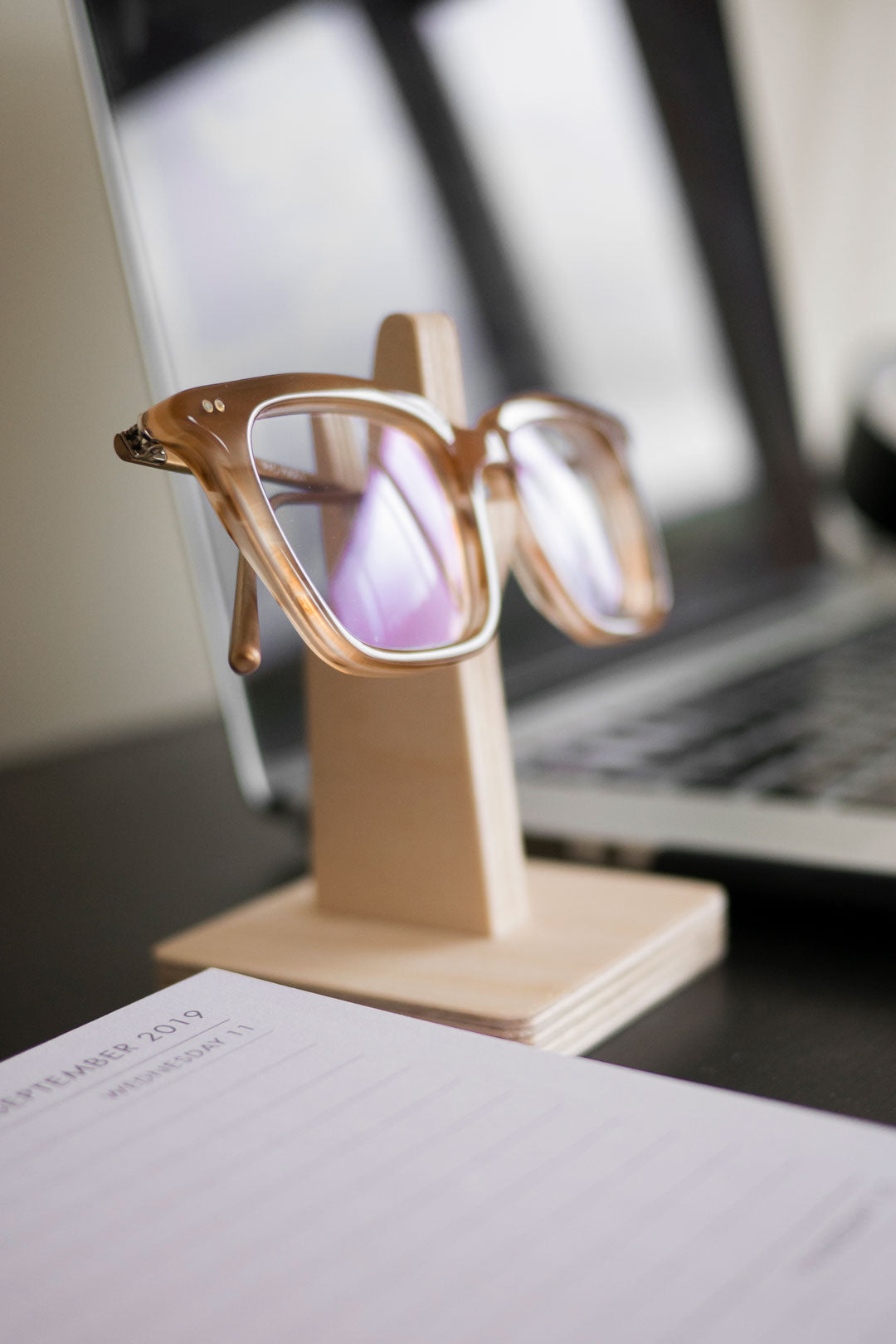 Amber glasses resting on wooden eyeglass stand on workdesk