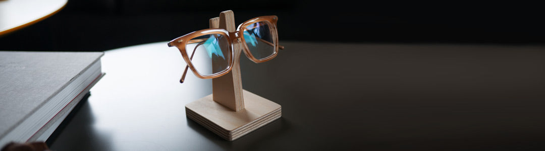 Amber spectacles resting on wooden glasses holder
