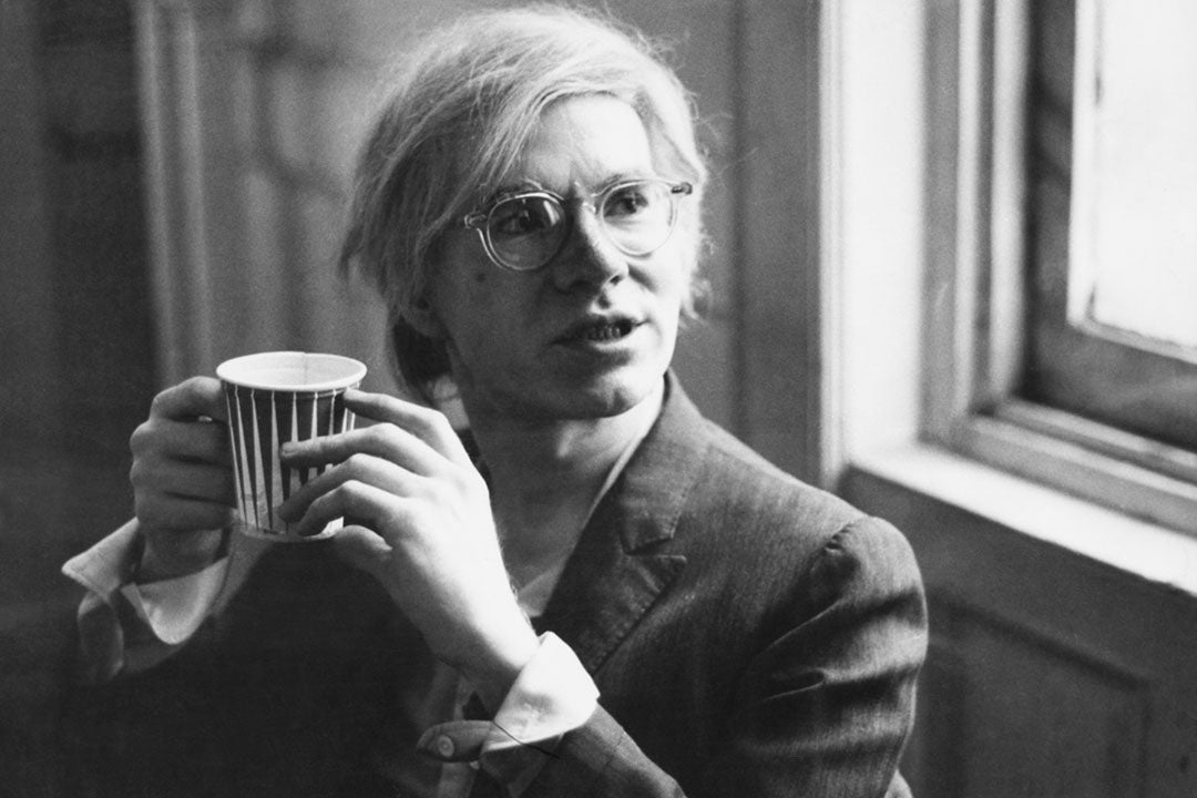 Andy Warhol drinking coffee wearing a suit and clear glasses frame
