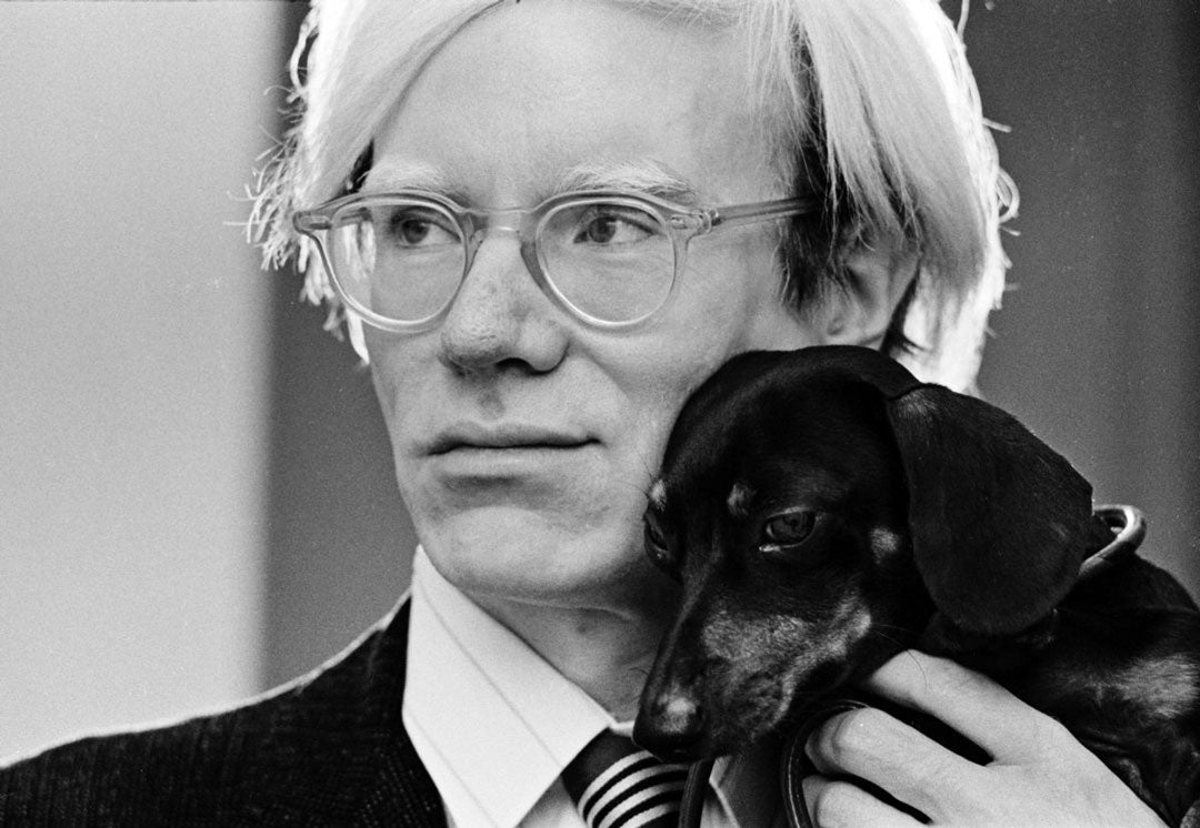 Andy Warhol holding his pet dog to his face