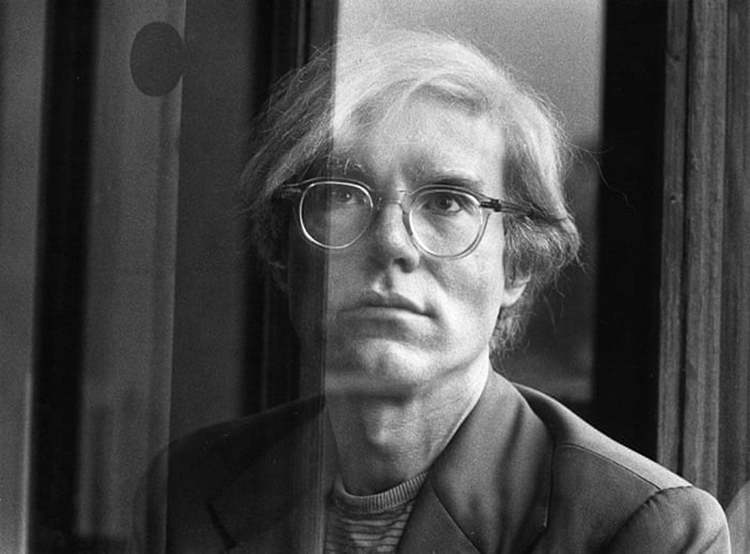 Andy Warhol looking through glass window wearing his clear frame spectacles