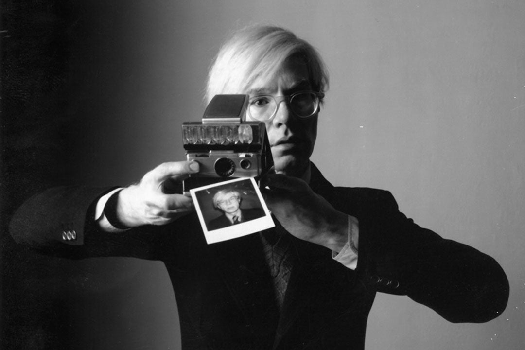 Andy Warhol taking a picture with a polaroid camera