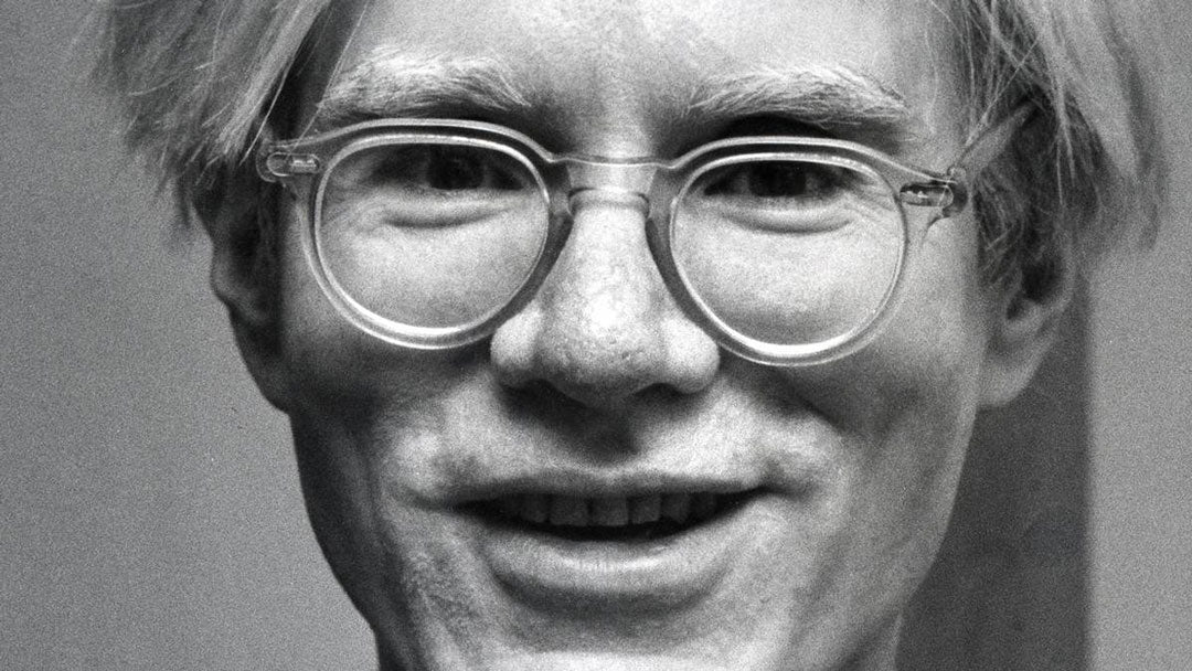 Andy Warhol wearing his clear glasses frames smiling