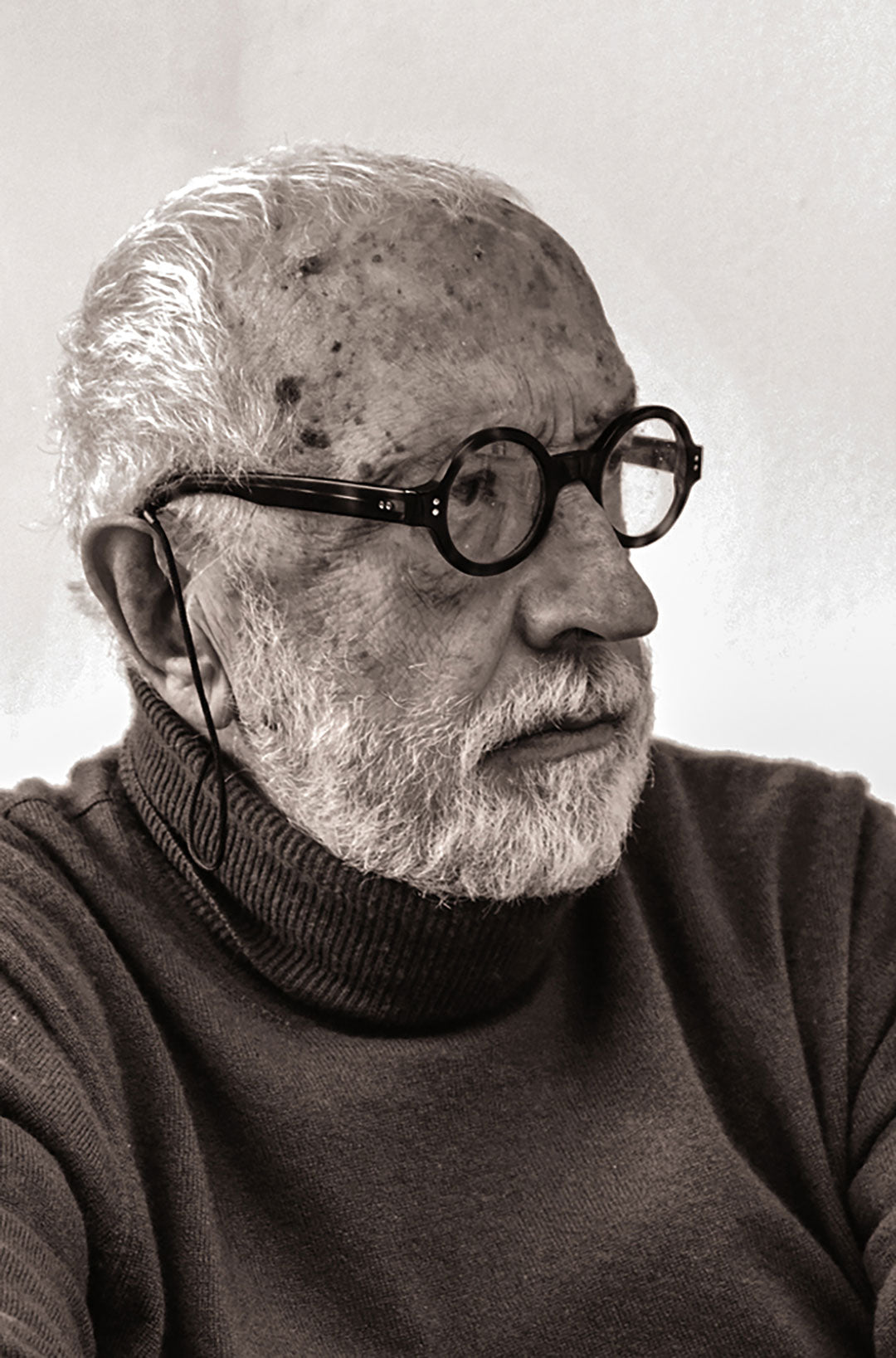 Architect Andrea Branzi wearing round speckled glasses frame