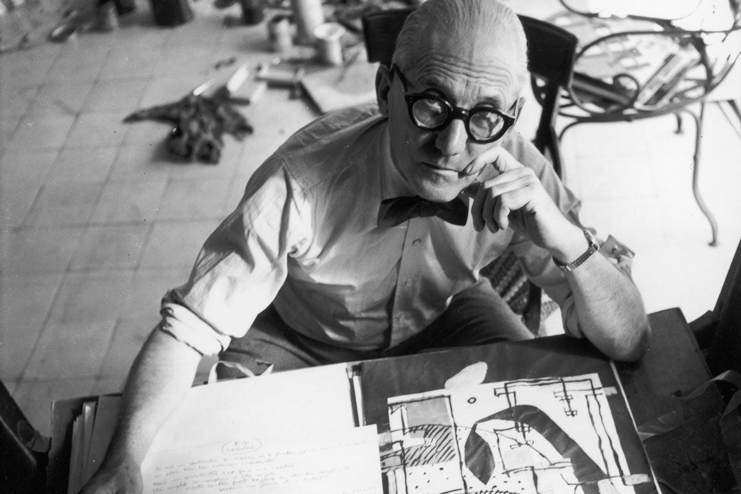 Arcitect Le Corbusier looking upwards from his work desk through his thick frame glasses
