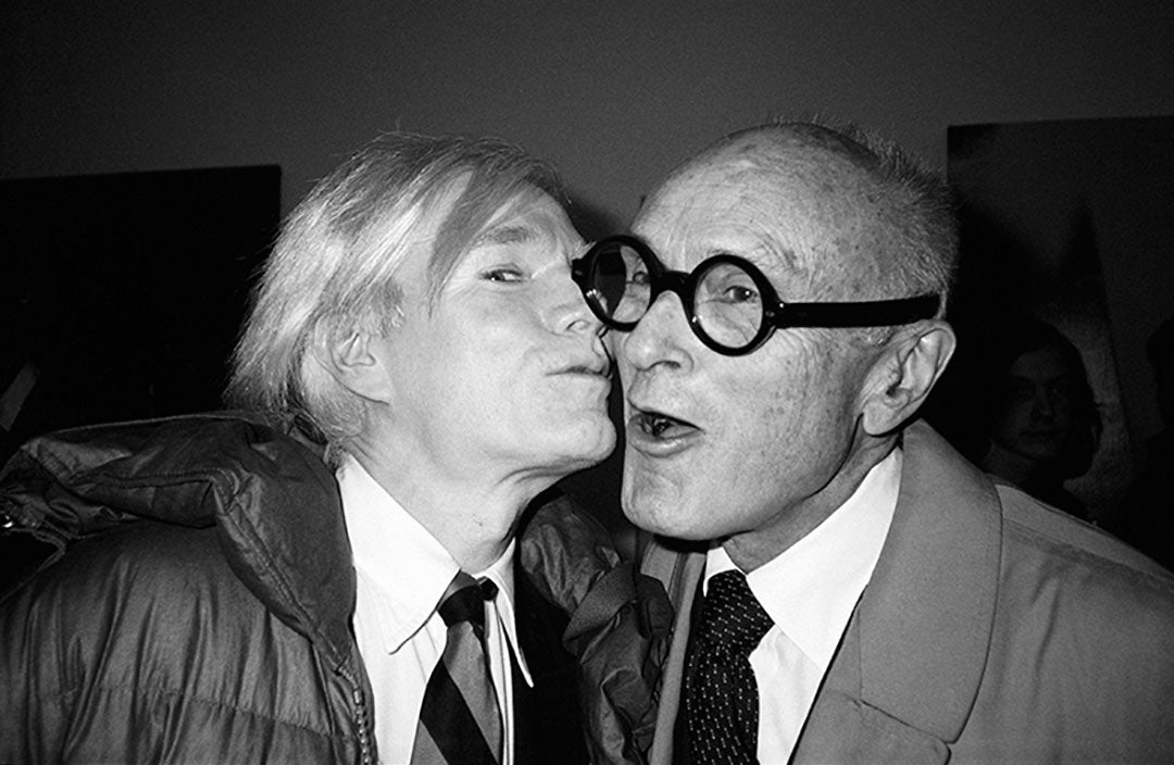 Artist Andy Warhol kissing architect Philip Johnson