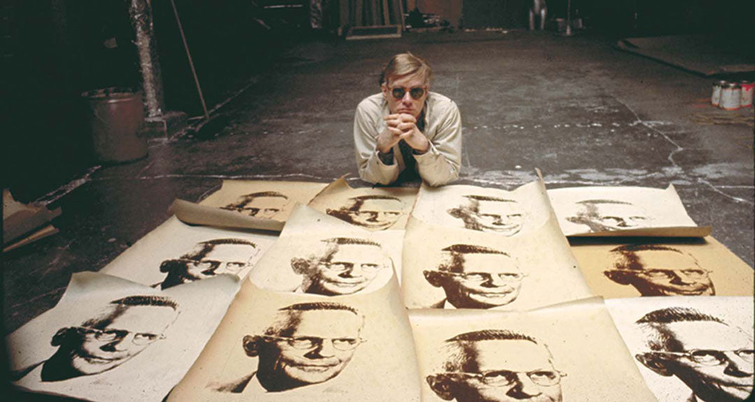 Artist Andy Warhol lying down in his studio wearing sunglasses