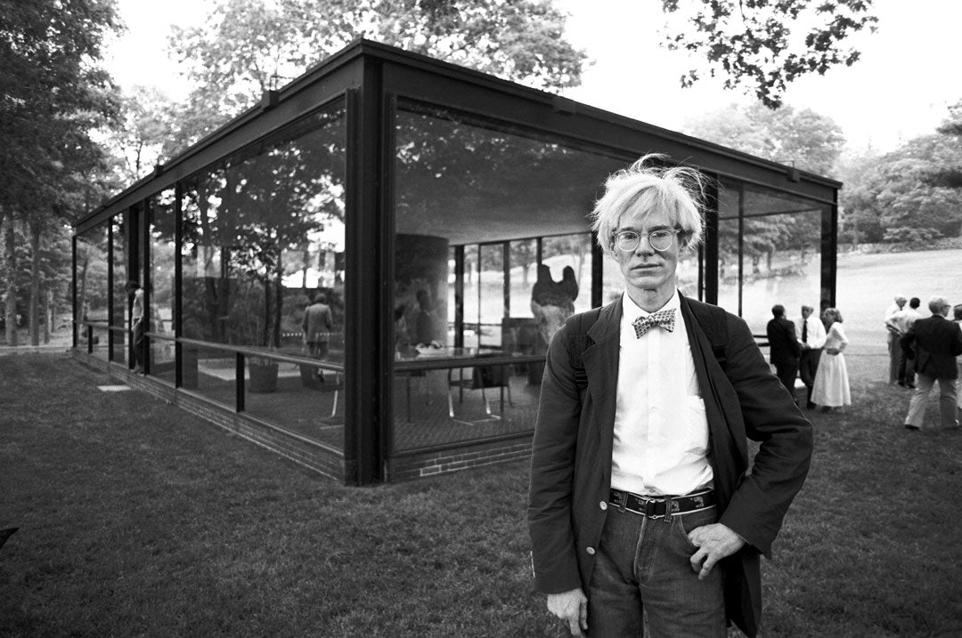 Artist Andy Warhol wearing suit and bow tie outside glass building