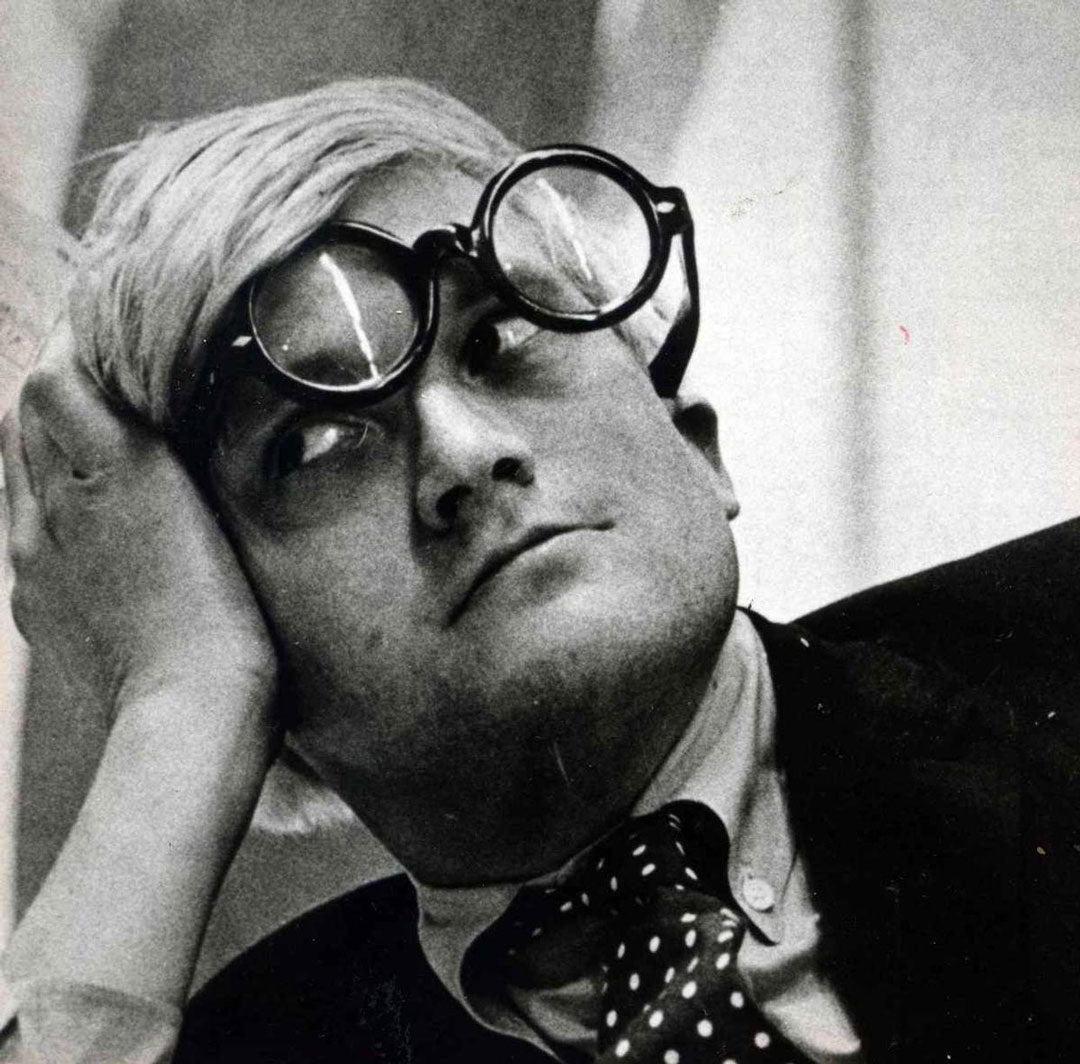 Artist David Hockney resting his head in his hand wearing round black spectacles