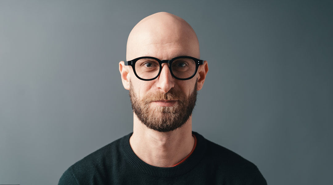 Bald man wearing black glasses frame