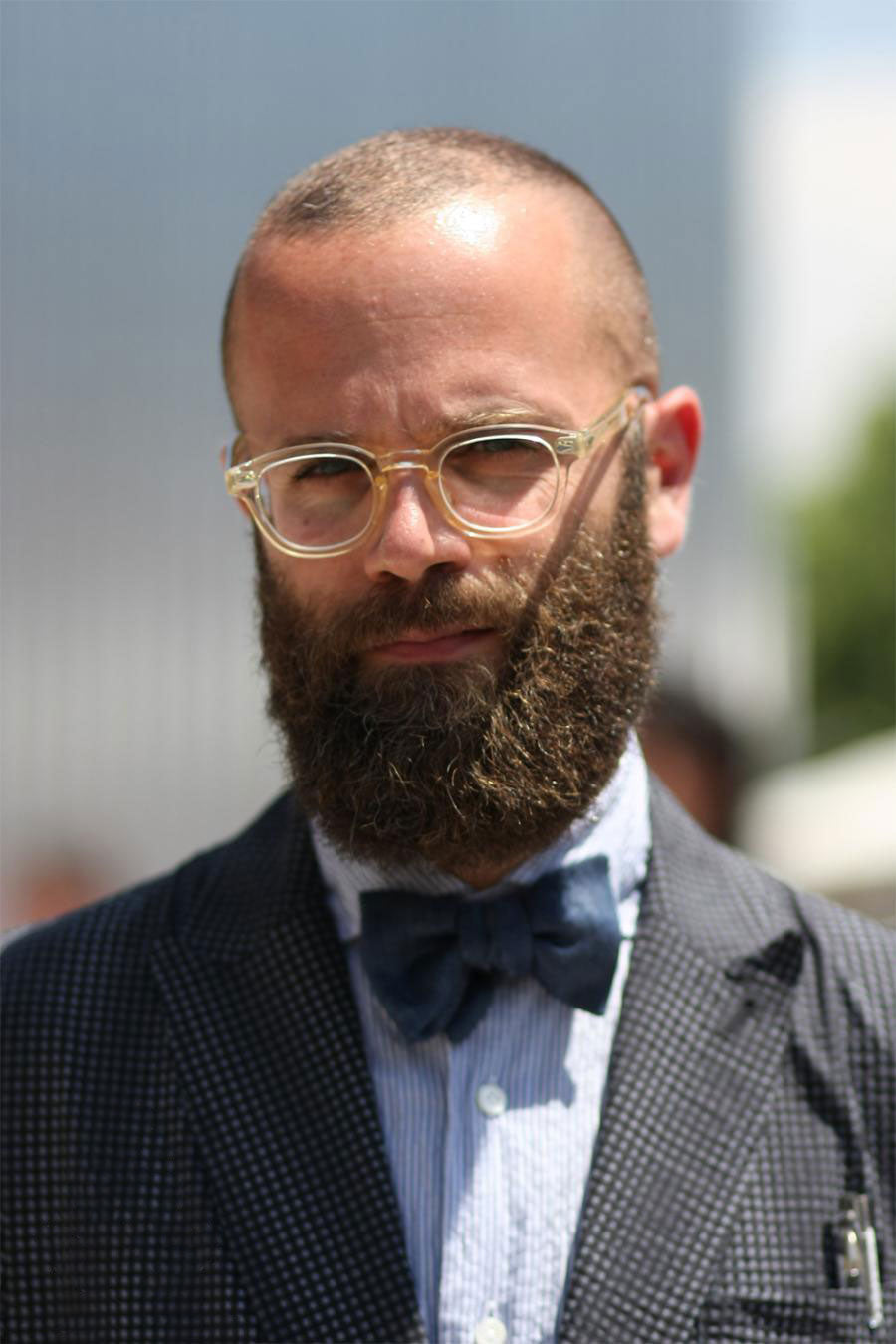 Bearded bald man wearing semi opaque thick glasses frame