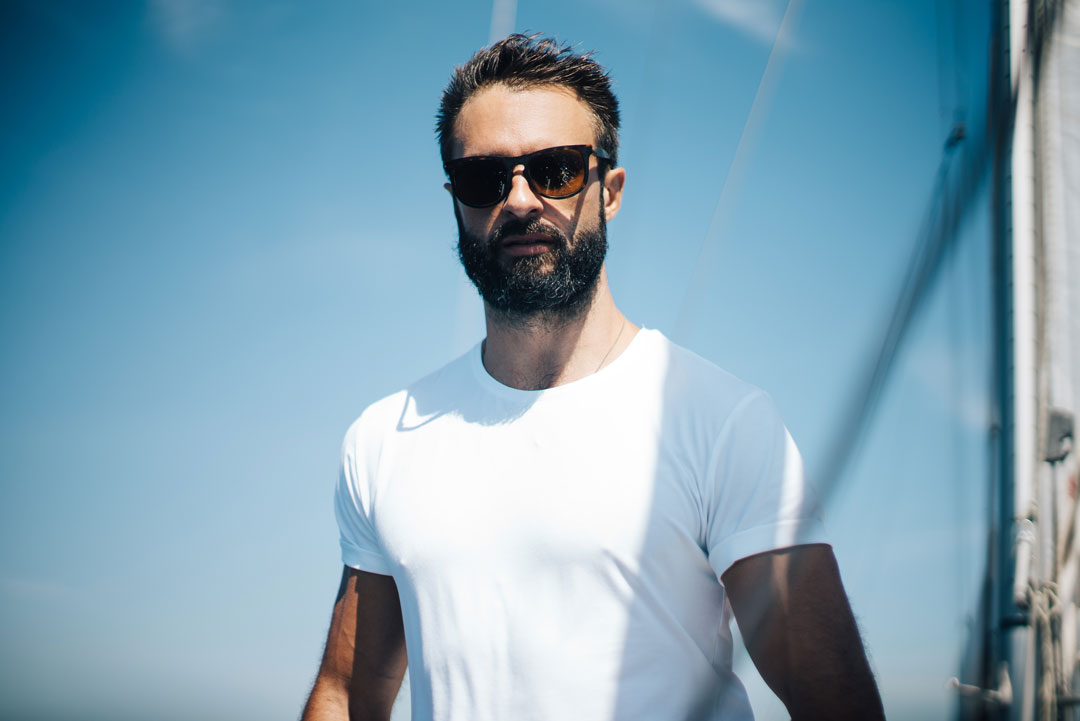 Bearded man facing viewer on yacht wearing varifocal sunglasses and white Tshirt