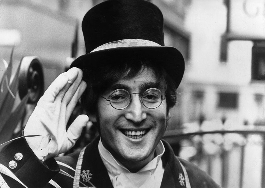 Beatles singer John Lennon saluting wearing white gloves top hat and round spectacles smiling