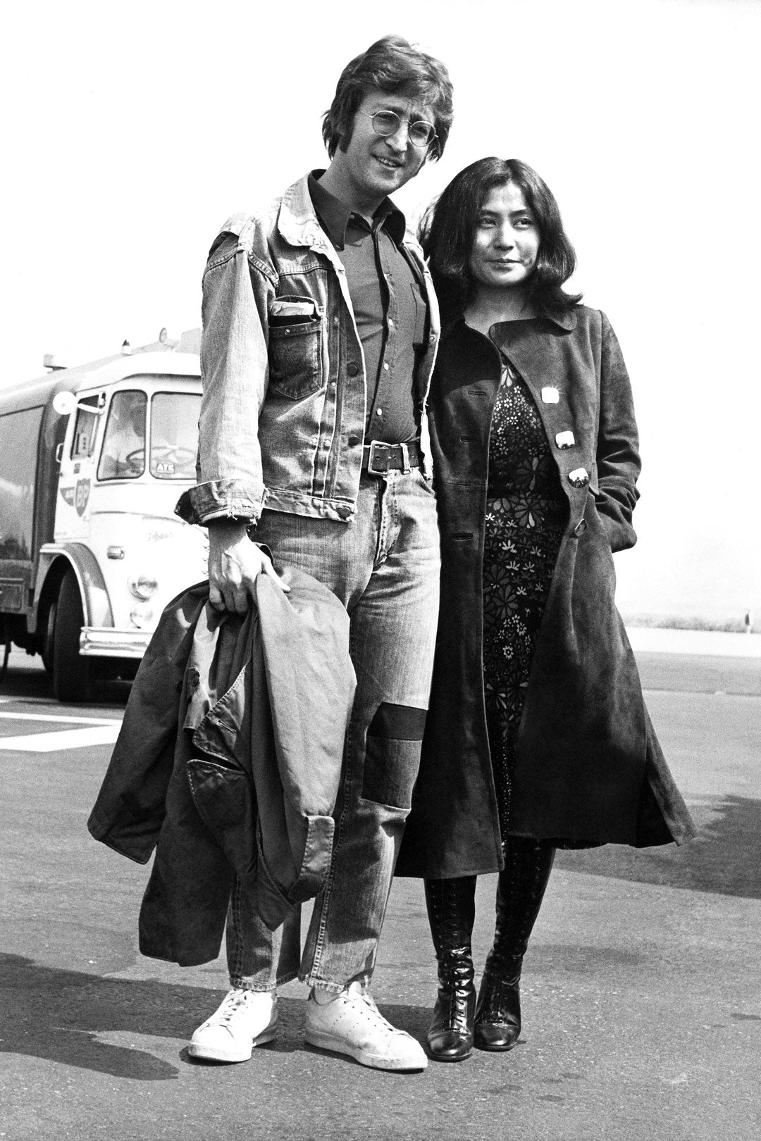 Black and white photograph of John Lennon and Yoko standing together in front of bus at airport
