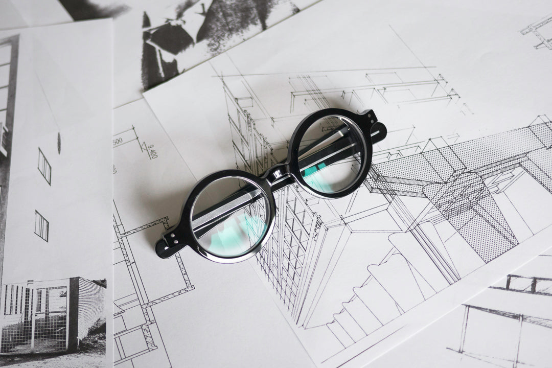 Black architect spectacles lying folded on top of drawings