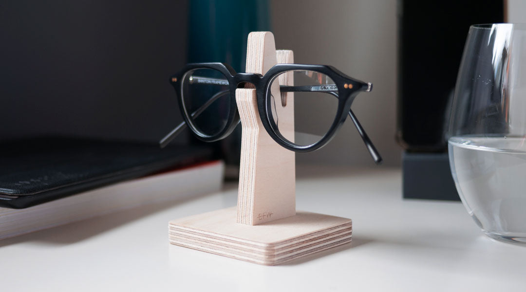 Black circle glasses on wooden glasses holder