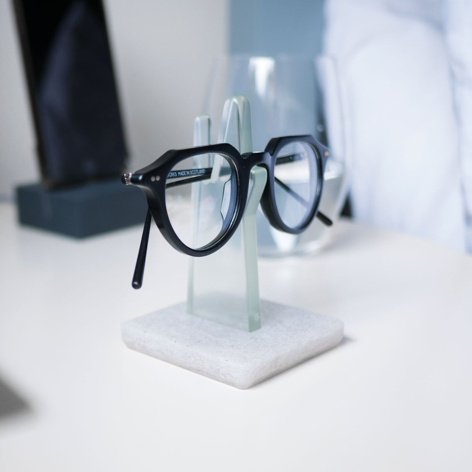 Black glasses frame resting on green spectacle holder